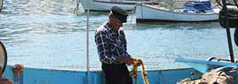 A Greek traditional fisherman, fixing his hets before he sails out to sea for the day.